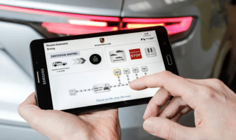 A tablet is used to maneuver the sports car via autonomous driving technology to the correct position in the Porsche workshop, quickly and automatically